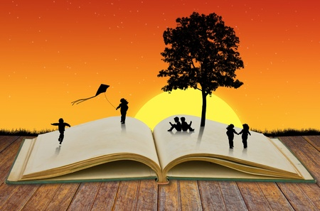 Silhouettes of children playing on old book with tree photo