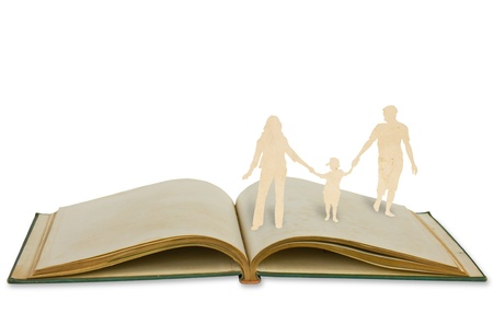 Paper cut family symbol on old book isolated on white background. photo
