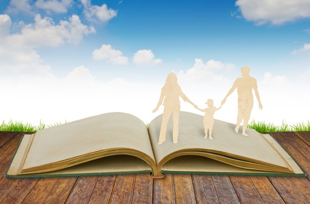 Paper cut family symbol on old book with blue sky photo