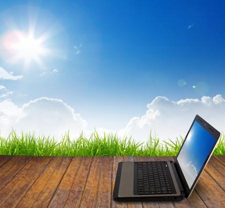Laptop na podłogi drewnianej z zielonej trawie Zdjęcie Seryjne