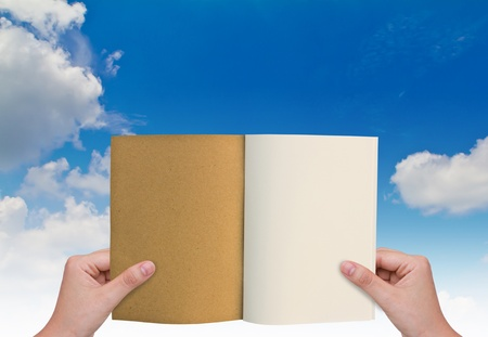 double page spread: Hands holding book in sky