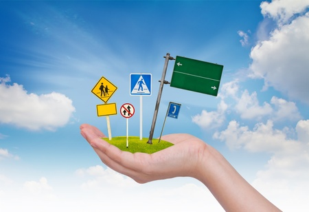 Road sign in hand over blue sky photo