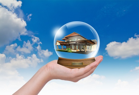 Hand hold snow-dome with home inside against a blue sky Stock Photo - 10944810