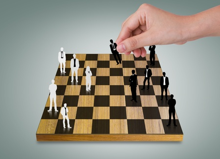 Hand Playing chess game with Silhouettes of business people photo