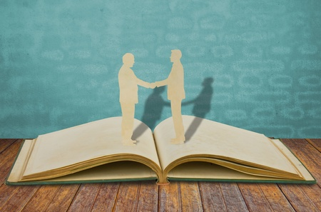 Paper cut of two business man shake hand on old book Stock Photo - 10901179