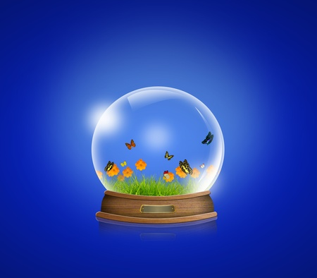 snow-dome with Yellow flowers, green grass and butterfly inside against a blue background photo