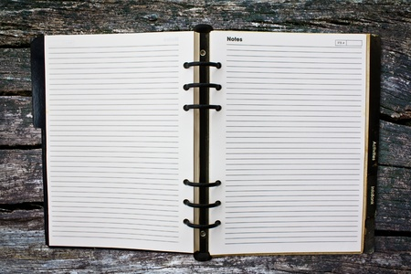 Old notebook (blank paper) on wood wall. Stock Photo - 11489527