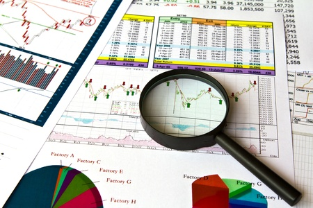 A magnifying glass focusing on a graph in the financial charts photo