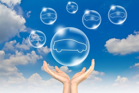 Hand hold Bubbles in the sky with car inside photo