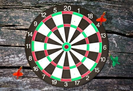Dartboard on wood wall (miss darts) photo