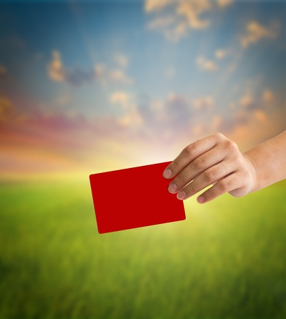 arbitrator: Hand holding a red card