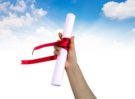 graduation background: Hand holding Diploma wrapped with a red ribbon.