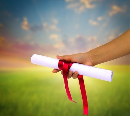 赤いリボンで包まれた卒業証書を持っている手。