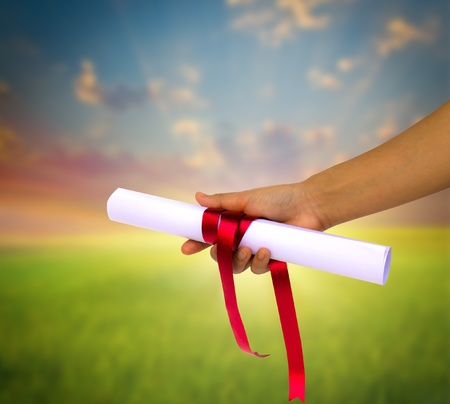 certificate bow: Hand holding Diploma wrapped with a red ribbon.
