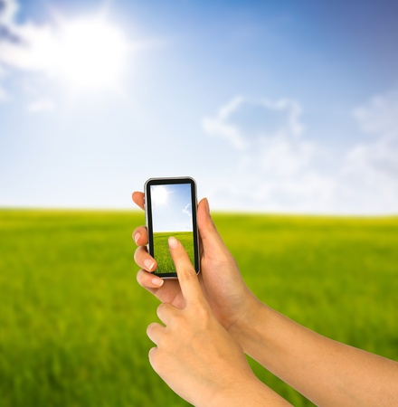 Cell phone in hand and country view of sunny day photo