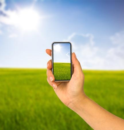 Mobiele telefoon in de hand en het land uitzicht op zonnige dag Stockfoto