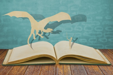 Paper cut of dragon and child hold sword on old book photo
