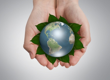 royalty: Environmental conservation Concept: Hands holding earth on leaf