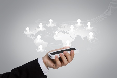 Businessman holding mobile phone with social network photo