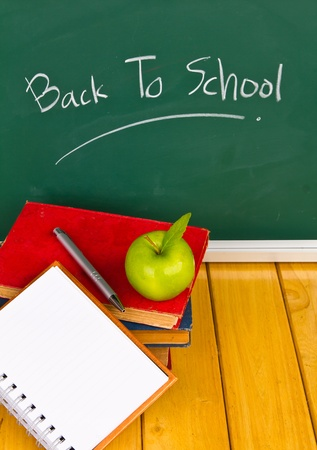 Back to school written on chalkboard with green apple and books photo