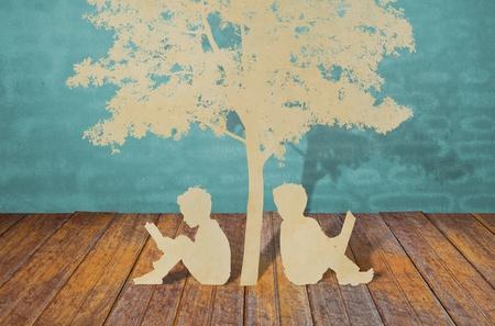 under the tree: Cortar el papel de los ni�os a leer un libro bajo el �rbol