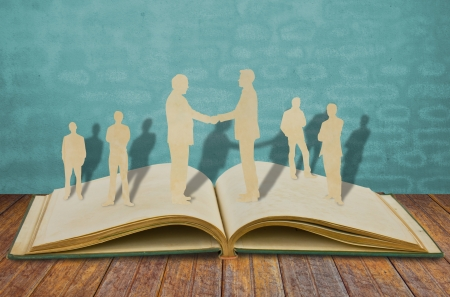Paper cut of two business man shake hand on old book Stock Photo - 11425225