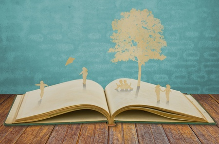 Paper cut of children play on old book photo