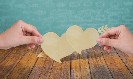 Hands with two paper heart and arrow photo