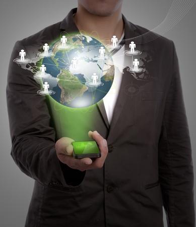 trabajo social: Mano que sostiene un programa de la Tierra de teléfono y red social