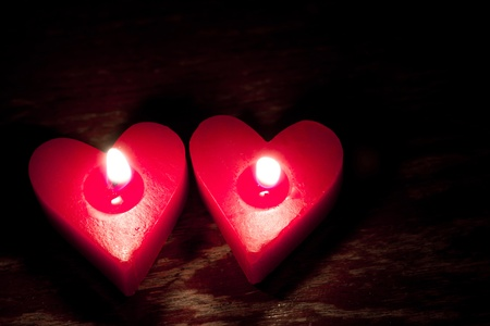 Red burning heart shaped candles photo