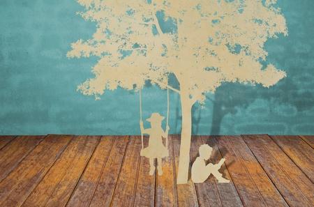 padres hablando con hijos: Cortar el papel de los ni�os a leer un libro y los ni�os en el columpio bajo el �rbol Foto de archivo