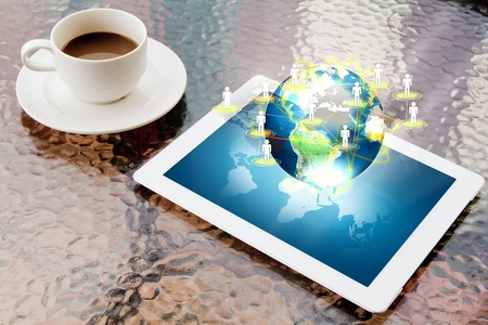 Tablet PC and coffee on table  shows social network surrounding earth photo