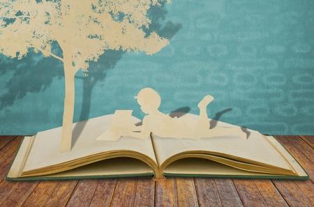 under the tree: Corte del papel de los ni�os a leer un libro bajo un �rbol en el libro viejo