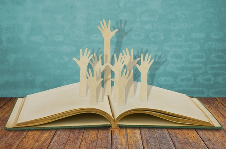 participate: Paper cut of Hands volunteering or voting on old book