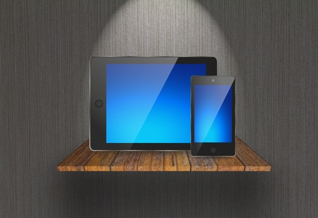 Touch pad and  phone on  wood shelf photo