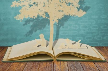 paper cut: Paper cut of children read a book  on old book