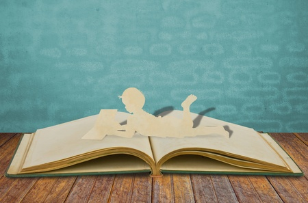 Paper cut of children read a book  on old book photo