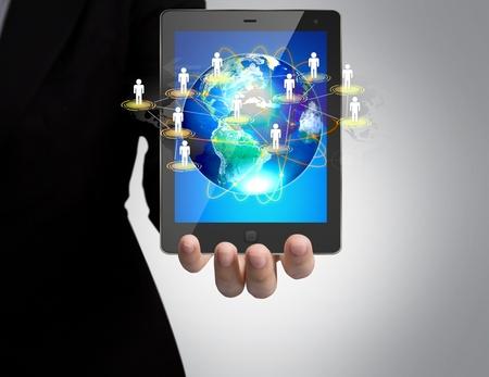 sozialarbeit: Hand h�lt ein Touch-Pad Show Erde und soziales Netzwerk Lizenzfreie Bilder