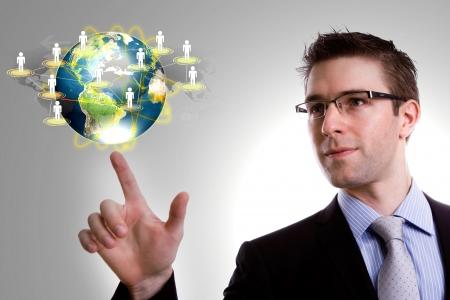 SpoÅ'ecznego koncepcja sieci: mÅ'ody czÅ'owiek biznesu ziemia punkt sieci spoÅ'ecznej Zdjęcie Seryjne