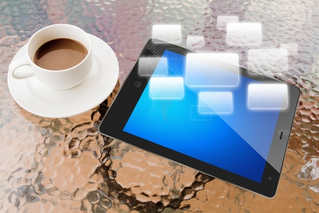 Digital tablet and cup of coffee on work table photo