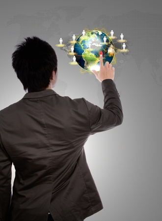 Back view of a young business man pointing at earth of social network photo