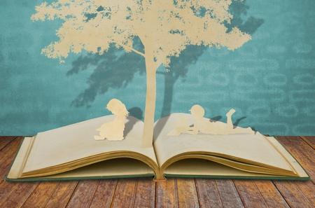Corte del papel de los niños a leer un libro bajo un árbol en el libro viejo