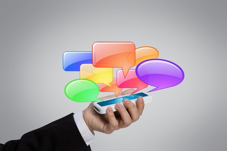 Business hand holding mobile phone with chat bubble photo