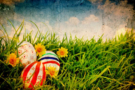 Grunge paper with Easter Eggs and flower on Fresh Green Grass over blue sky photo