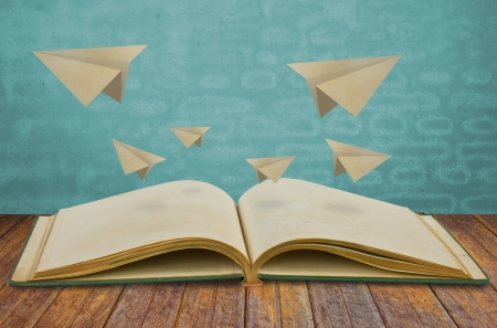 turning page: Magic book with paper plane Stock Photo