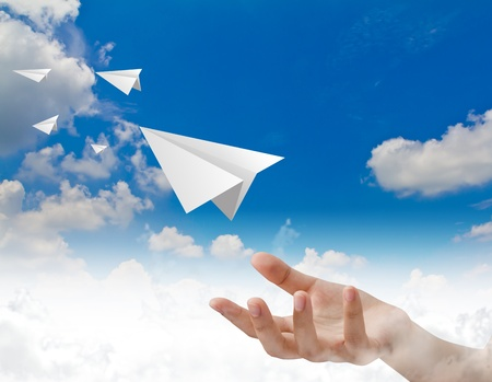 toy plane: Hand throwing a paper plane in the sky