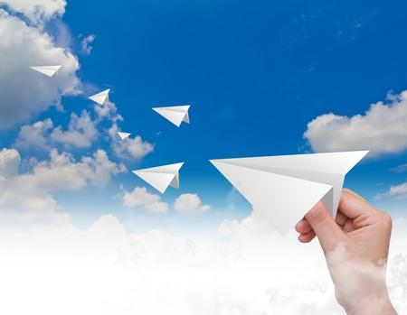 Hand het gooien van een papieren vliegtuig in de lucht