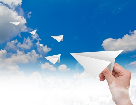 Hand throwing a paper plane in the sky Stock Photo - 12775763