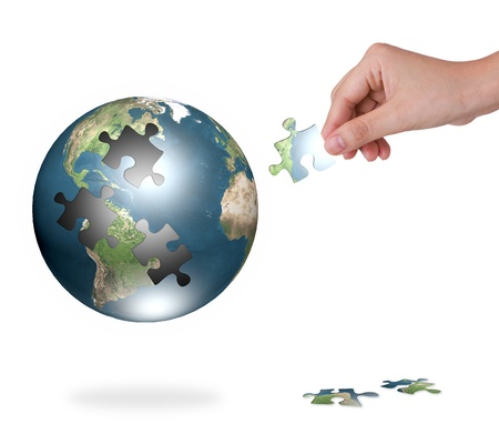 Business concept with a hand building puzzle globe Stock Photo - 12946704