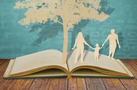 techniek: Papier gesneden van de familie symbool onder boom op oude boek Stockfoto